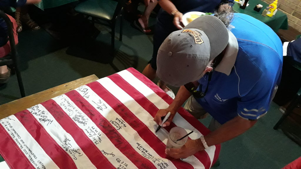Tony Priu sigs the flag to be given to Team Australia